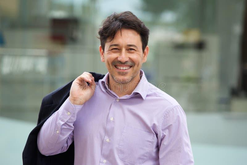 Homem de sorriso que guarda o revestimento sobre o ombro na cidade foto de stock royalty free