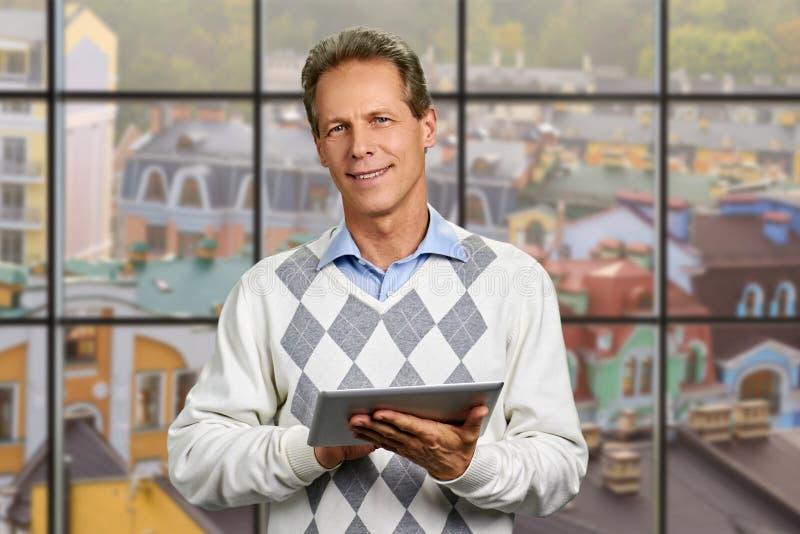 Homem de sorriso que guarda a tabuleta digital foto de stock