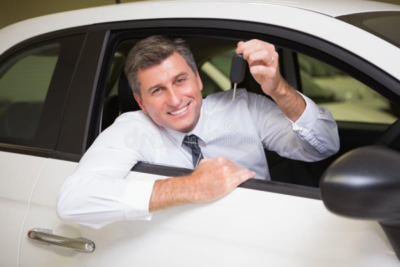 Homem de sorriso que guarda um assento chave do carro em seu carro fotografia de stock royalty free
