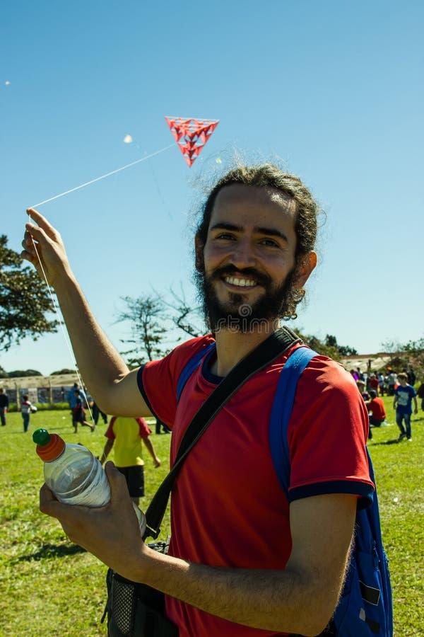 Homem de sorriso que joga com um papagaio fotografia de stock