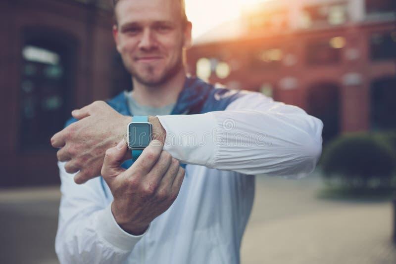 Homem de sorriso que mostra seus relógios espertos no pulso imagens de stock