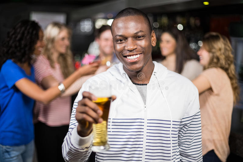 Homem de sorriso que mostra uma cerveja com seus amigos fotografia de stock royalty free