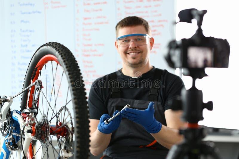 Homem de sorriso que repara o ciclo da montanha com chave inglesa imagem de stock
