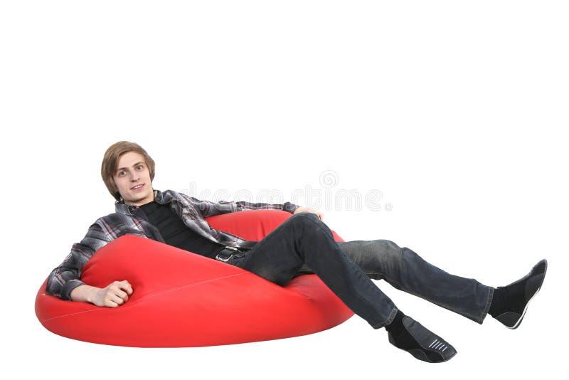Homem de sorriso que senta-se no saco de feijão imagem de stock royalty free