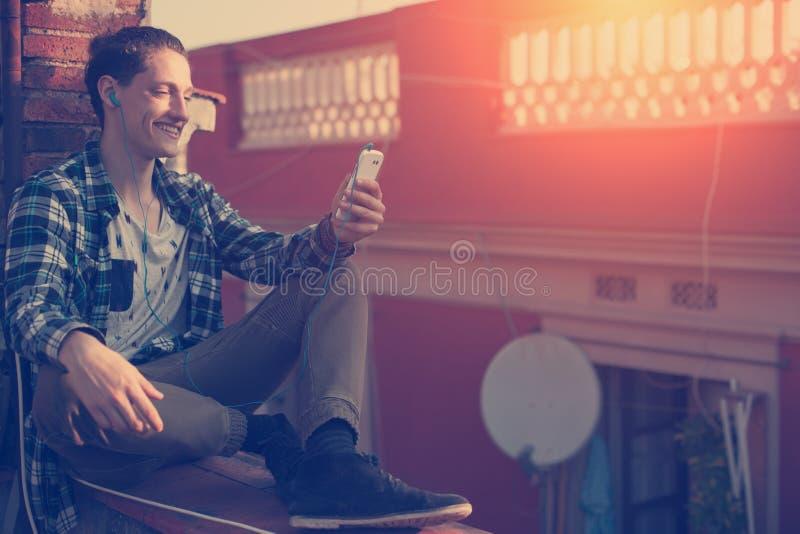 Homem de sorriso que senta-se no telhado com telefone celular e música de escuta fotografia de stock