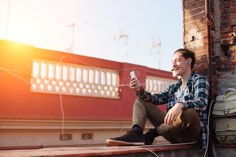 Homem de sorriso que senta-se no telhado com telefone celular e música de escuta nos fones de ouvido foto de stock