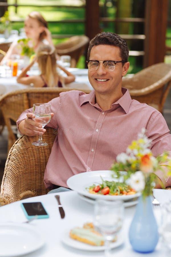Homem de sorriso que sente relaxado ao ter o jantar fotografia de stock