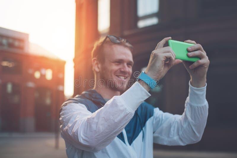 Homem de sorriso que toma a foto com o smartphone na rua fotografia de stock royalty free
