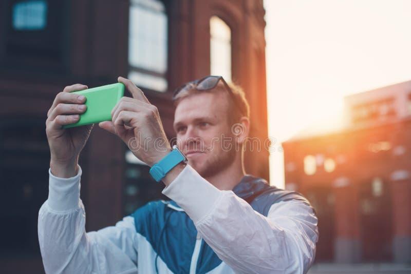 Homem de sorriso que toma a foto com seu smartphone na rua fotos de stock