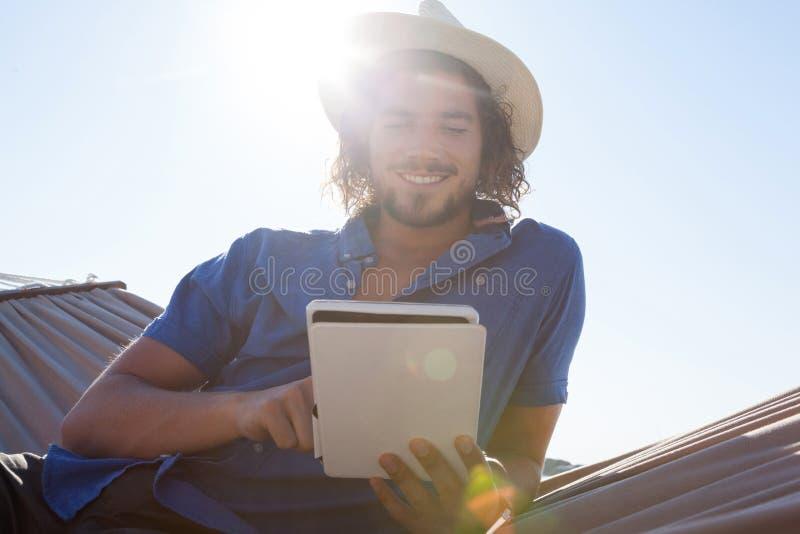 Homem de sorriso que usa a tabuleta digital na rede na praia fotografia de stock