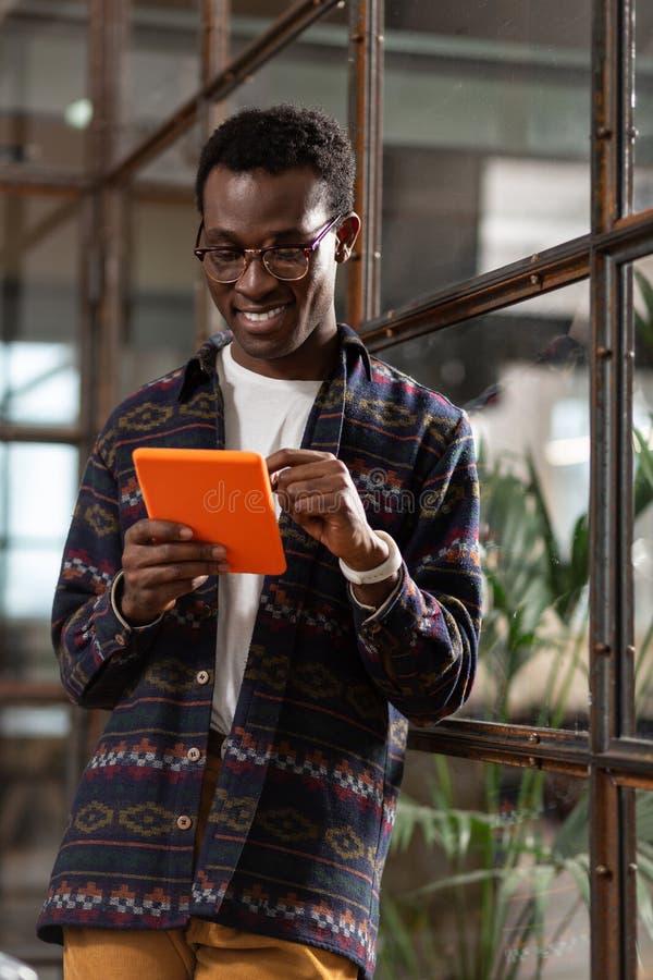 Homem de sorriso que usa uma tabuleta em um caso brilhante fotografia de stock