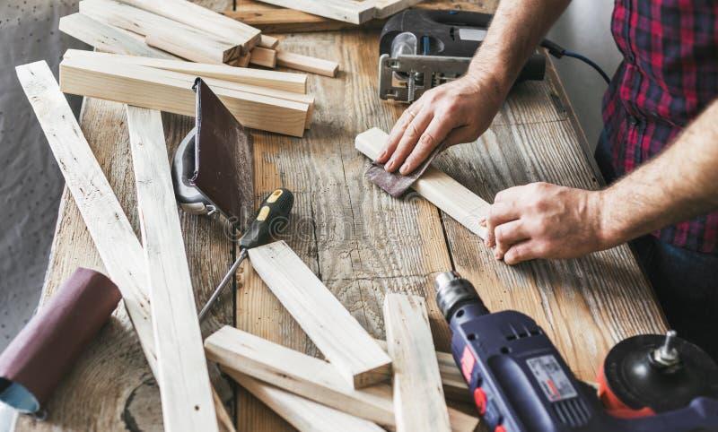Homem de trabalho da oficina da carpintaria do carpinteiro que lixa manualmente a prancha imagem de stock royalty free