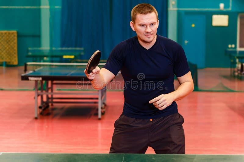 Homem de trinta anos no uniforme preto dos esportes que joga o t?nis de mesa no gym fotos de stock royalty free
