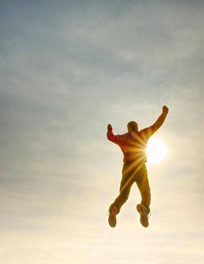Homem de vôo Silhueta do céu de salto do homem e do por do sol Alargamento de Sun foto de stock