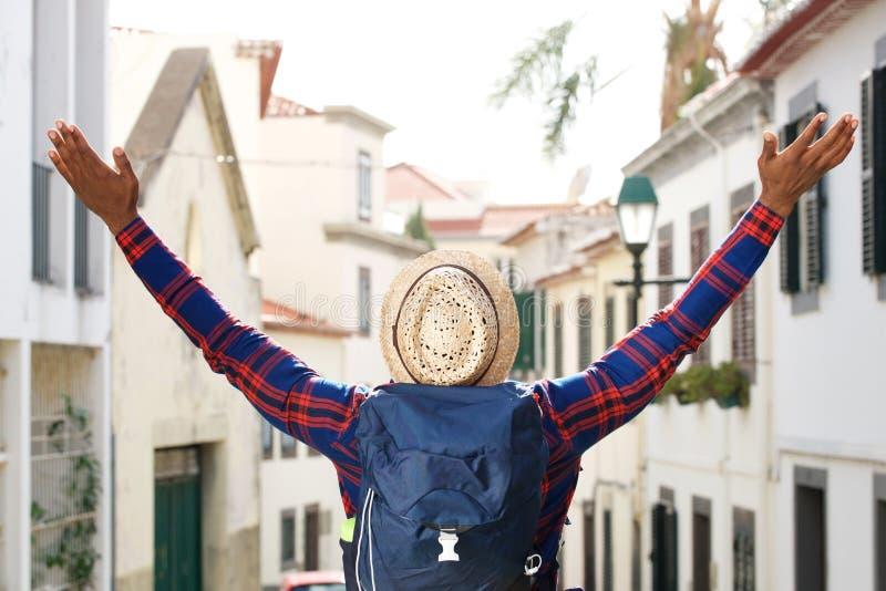 Homem de viagem preto com o chapéu e a trouxa que aumentam os braços na cidade fotografia de stock
