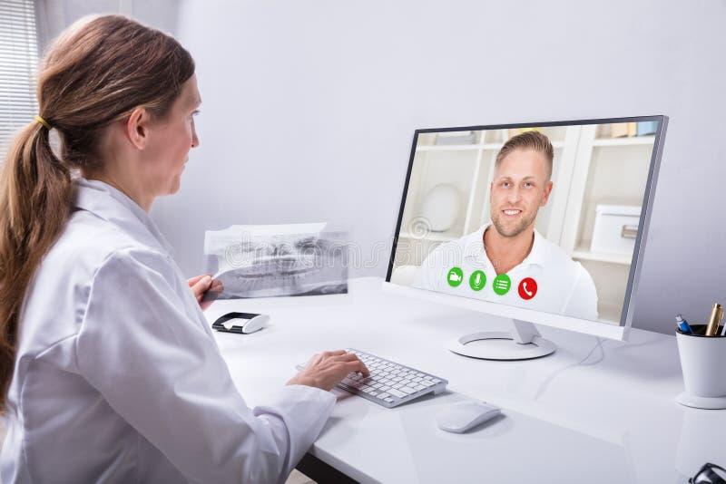 Homem de Video Conferencing With do dentista no computador fotos de stock