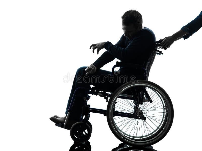 Homem deficiente deficiente na silhueta da cadeira de rodas fotografia de stock