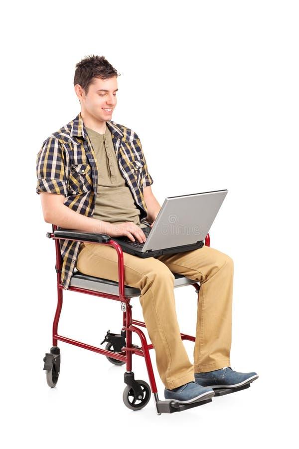 Homem deficiente dos jovens em uma cadeira de rodas que trabalha em um portátil foto de stock royalty free