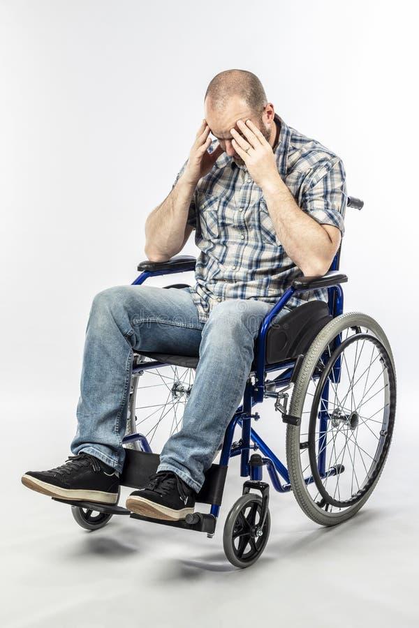 Homem deficiente em uma cadeira de rodas desesperada e triste fotografia de stock