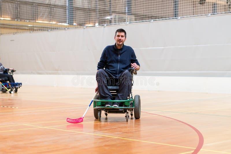 Homem deficiente em uma cadeira de rodas el?trica que joga esportes, h?quei do powerchair IWAS - Cadeira de rodas e amputado inte imagem de stock royalty free