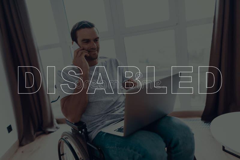 Homem deficiente em uma cadeira de rodas usando o portátil fotografia de stock