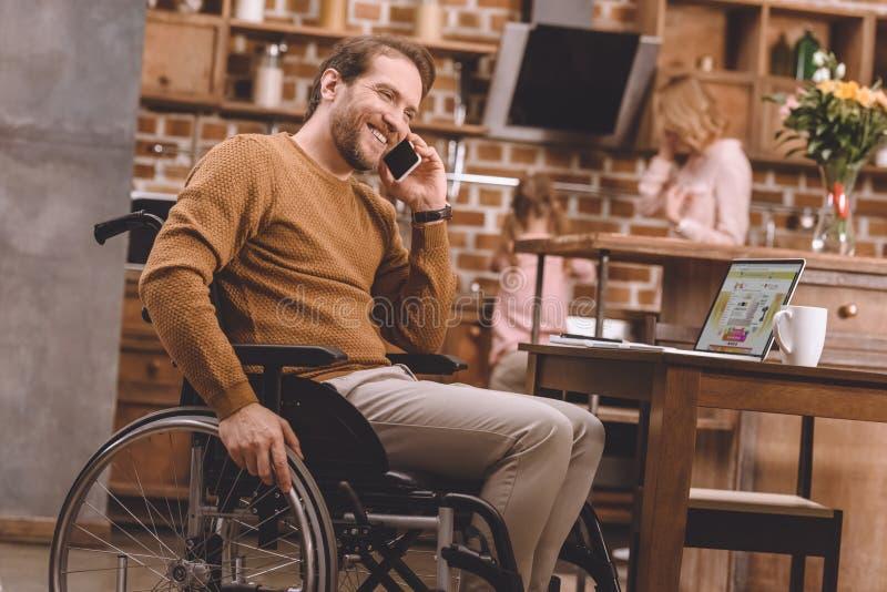 homem deficiente feliz na cadeira de rodas que fala no smartphone e que usa o portátil fotografia de stock royalty free
