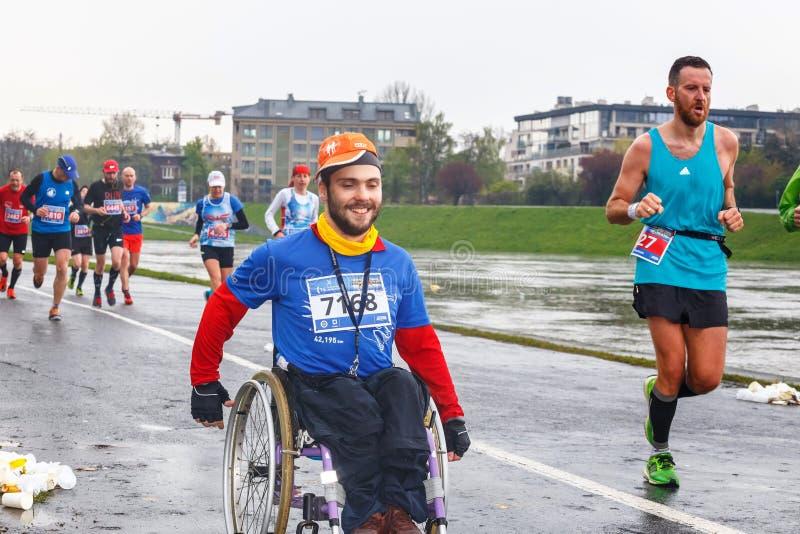 Homem deficiente não identificado na maratona em uma cadeira de rodas nas ruas da cidade fotos de stock