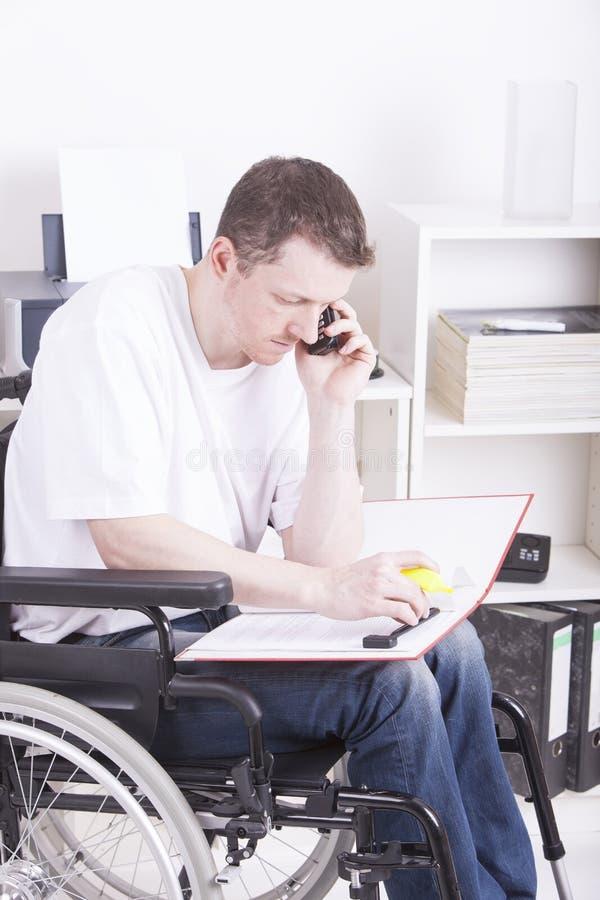 Homem deficiente na cadeira de rodas em um escritório domiciliário foto de stock