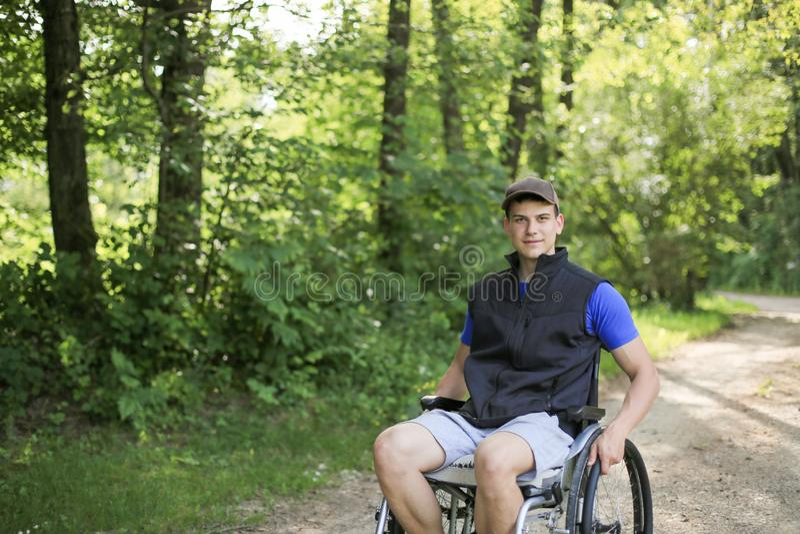 Homem deficiente na cadeira de rodas na natureza imagem de stock