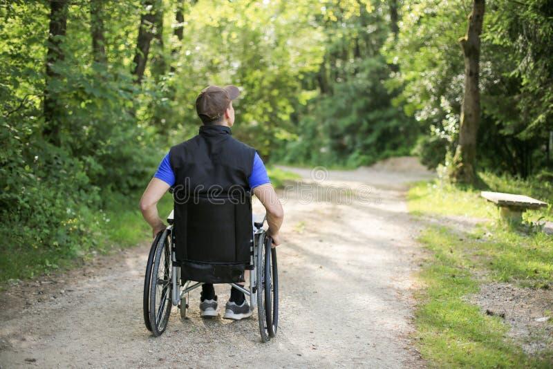 Homem deficiente na cadeira de rodas na natureza imagens de stock