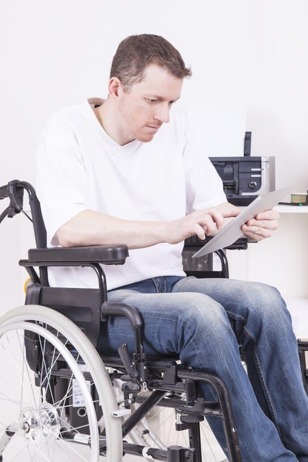 Homem deficiente na cadeira de rodas no trabalho fotografia de stock