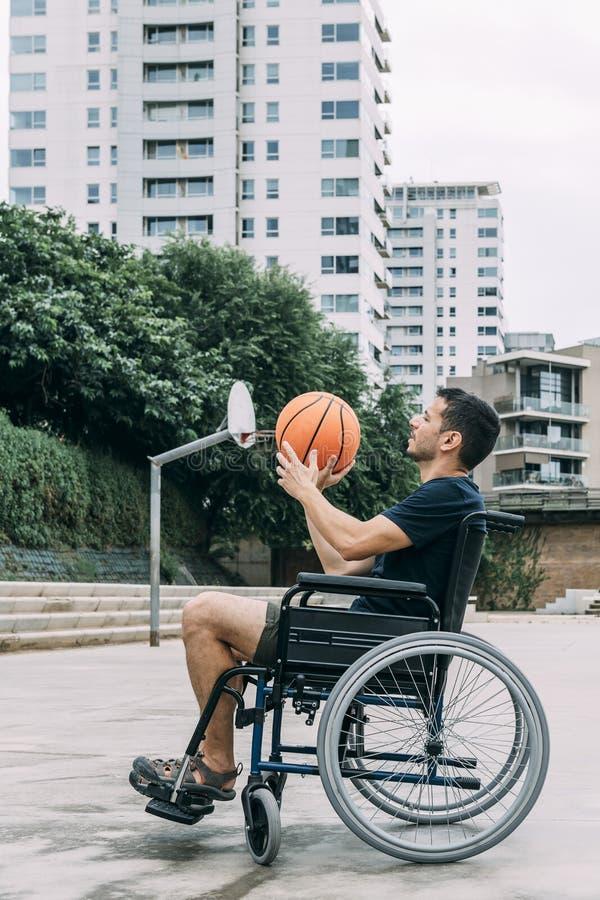 Homem deficiente na cadeira de rodas que joga o basquetebol imagem de stock