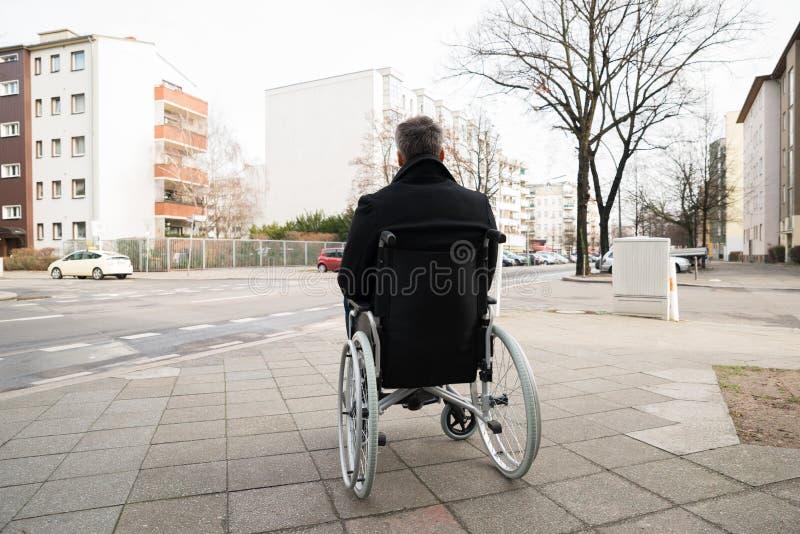 Homem deficiente na cadeira de rodas que olha a rua fotos de stock