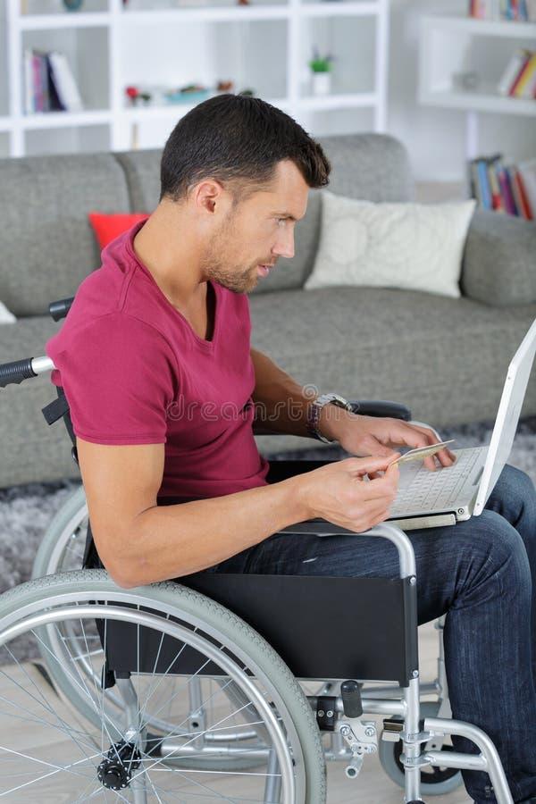 Homem deficiente na cadeira de rodas usando o portátil em casa imagem de stock