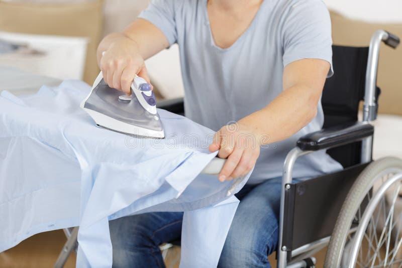 Homem deficiente na roupa passando da cadeira de rodas foto de stock royalty free