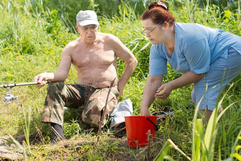 Homem deficiente que está sendo ajudado a pescar por sua esposa foto de stock