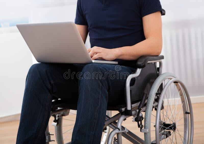 Homem deficiente que usa o portátil na cadeira de rodas foto de stock royalty free