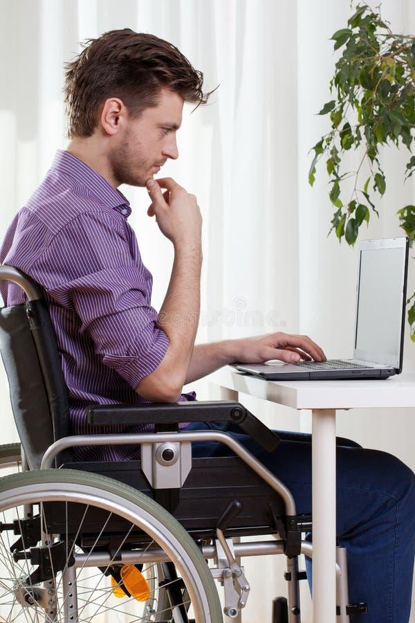 Homem deficiente que usa um portátil fotografia de stock royalty free