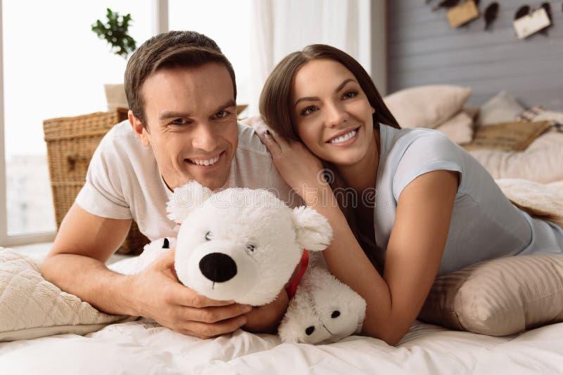 Homem deleitado alegre que guarda um urso macio fotografia de stock
