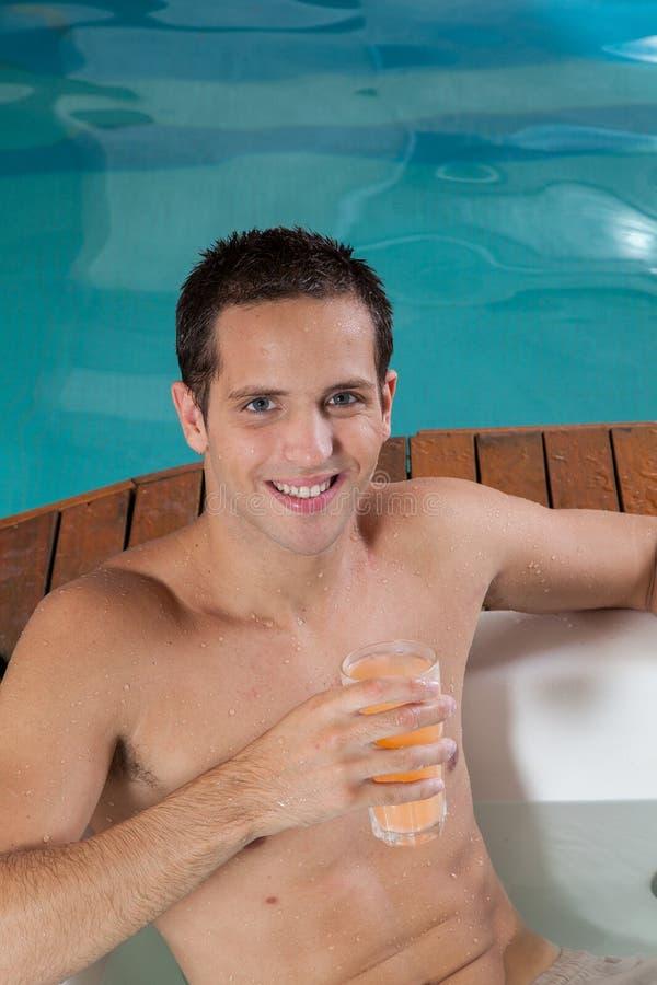 Homem dentro de um suco bebendo do Jacuzzi fotografia de stock
