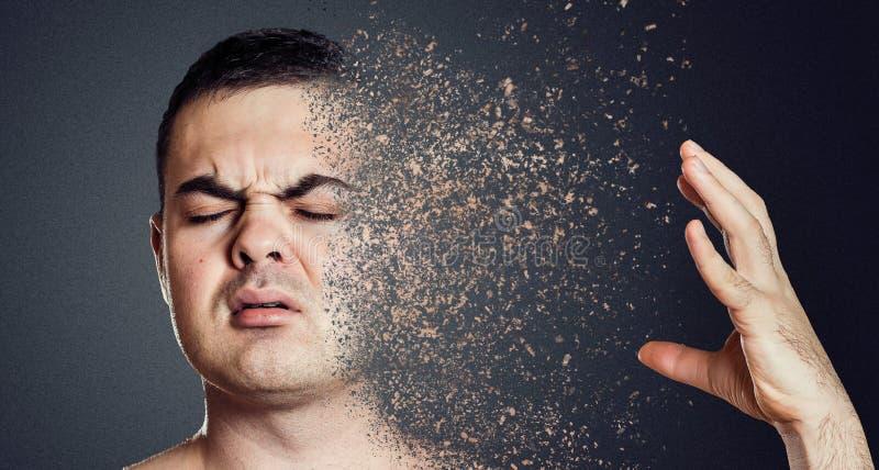 Homem depressivo que dissolve sua cara em partes Conceito da saúde mental fotos de stock