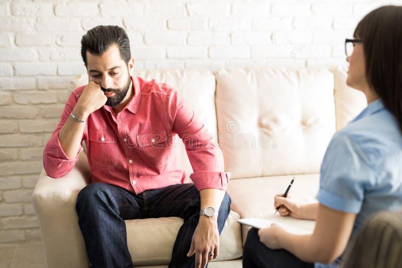 Homem deprimido durante a terapia no escritório do ` s do psicólogo fotos de stock