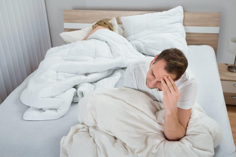 Homem deprimido na cama quando sono da mulher foto de stock
