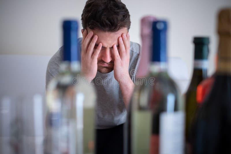 Homem deprimido que bebe o licor duro em casa fotografia de stock