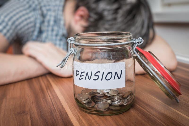 Homem deprimido que encontra-se na tabela Economias da pensão no frasco na parte dianteira fotografia de stock royalty free