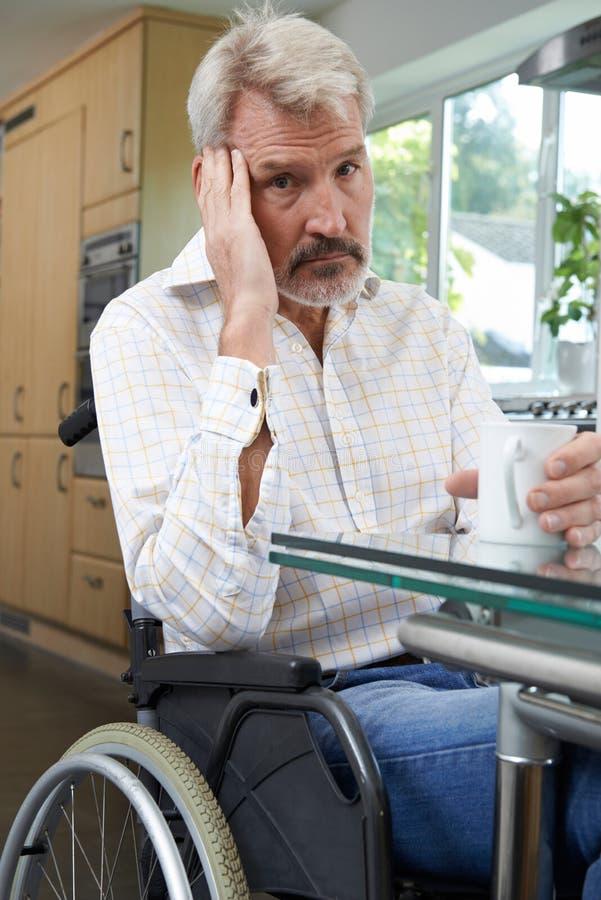 Homem deprimido que senta-se na cadeira de rodas em casa imagens de stock royalty free