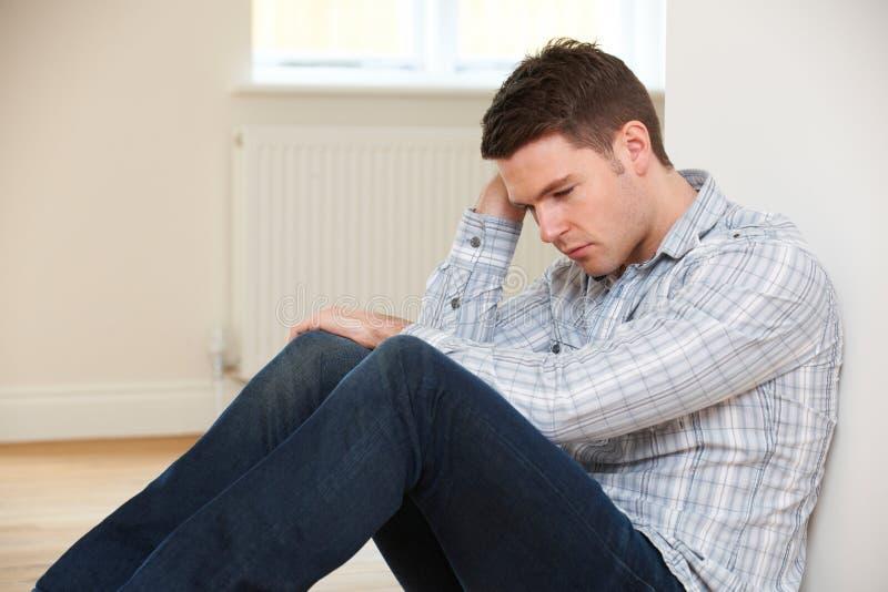 Homem deprimido que senta-se no assoalho da sala vazia fotografia de stock