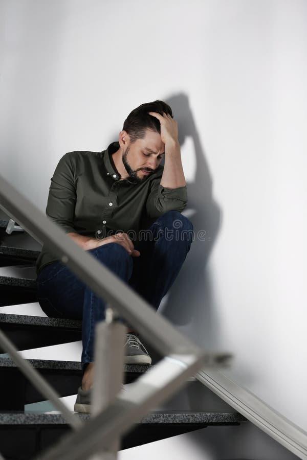 Homem deprimido só que senta-se em escadas fotografia de stock royalty free