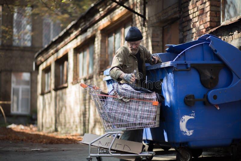 Homem desabrigado com carrinho de compras que recolhe garrafas vazias para reciclar imagem de stock royalty free