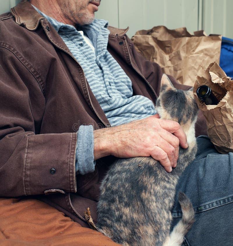 Homem desabrigado com frasco de vinho e o gato disperso imagens de stock royalty free